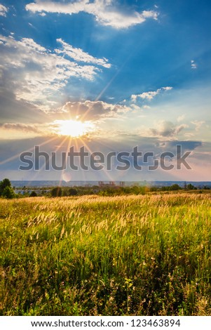 Sunset over a meadow. Evening rural landscape