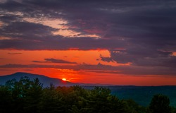 Sunset over a mountain peak. Mountain sunset peak. Red sunset landscape. Beautiful sunset sky clouds landscape