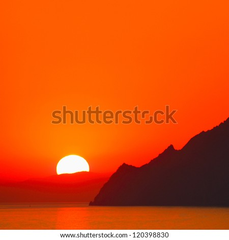 Sunset over a sea and mountains