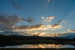 Sunset over a small Lake in the Colorado Rocky Mountains, known as Los Lagos Reservoir Number three. Near Kelly Dahl Campground and the Town of Nederland, CO.