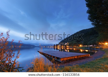 Sunset over a tranquil lake with a wooden jetty and colourful lights lining the shore