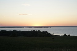 Sunset over a wide river. A summer evening background in pale grays and pinks against a dark green background. Copy space.