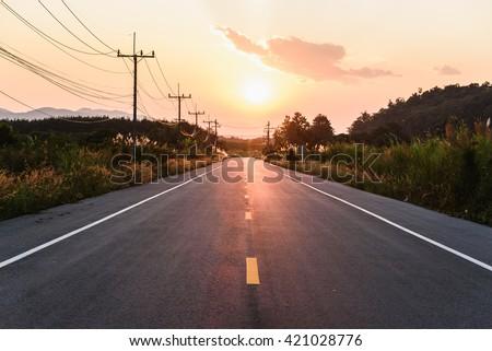 sunset over asphalt road #421028776