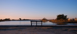 Sunset over Assateague Island over marshes, salt water bay with boardwalk and park bench.