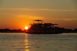 sunset over boat on Chobe river landscape, Botswana, Africa wilderness