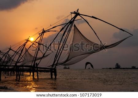 Sunset over Chinese Fishing nets and boat in Cochin (Kochi), Kerala, India.