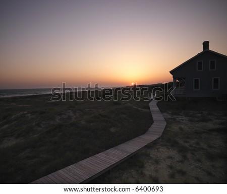 Sunset over coastal beach house with wooden boardwalk at  Bald Head Island, North Carolina. - stock photo