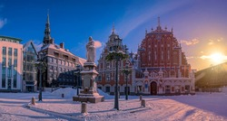 Sunset over covered in snow Riga Town Hall Square in winter in Riga, Latvia. View of  famous House of the Blackheads and Roland's Statue against blue sky with sunset lights.
