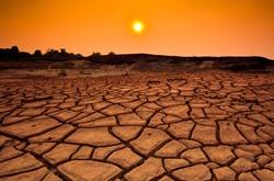 Sunset over cracked land and arid terrain