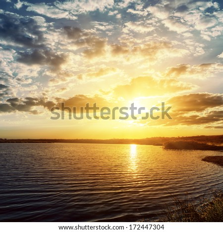 sunset over dark river