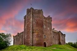 Sunset over Doune Castle in the Stirling district, Scotland. It is a medieval courtyard fortress built around 1400 by Robert Stewart, Duke of Albany, Regent of Scotland.