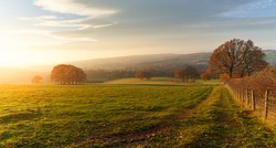 Sunset over farmland, meadows and trees in autumn with golden brown leaves on the trees in England, UK.