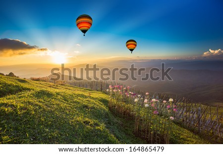 Sunset over forest mountain with hot air balloon - Shutterstock ID 164865479