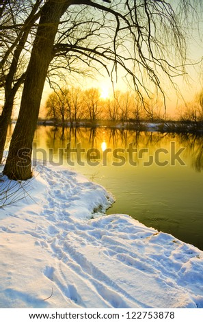 Sunset over frozen river in winter,
