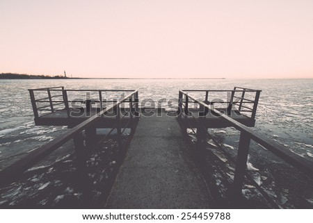 sunset over frozen sea with ice blocks and dramatic colorful sky with old metal bridge - vintage retro grainy film effect