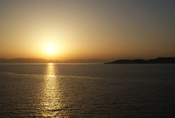 Sunset over Greek cost, water reflecting beam of light