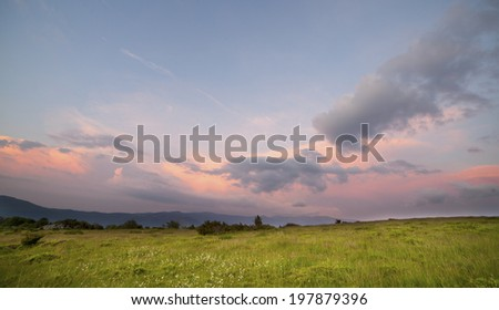 Sunset over green field #197879396