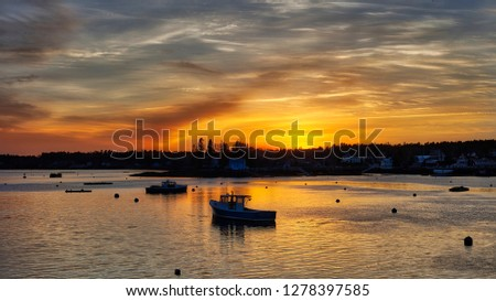 Sunset over harbor with lobster boats