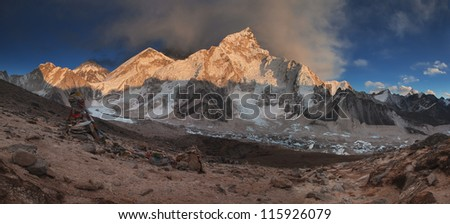 Sunset over Himalayas Mt Everest range with Buddhist prayer flags and stone shrine from Kala Patthar.