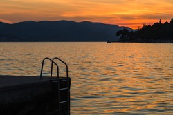 Sunset over inviting steps into the Peljesac channel used by beach goers between Orebic and Korcula Island.