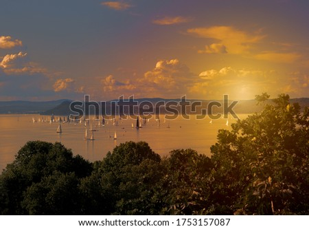 Sunset over Lake Balaton in Hungary with sailing boats on a summer afternoon, sailboat race, watersport, lake in the setting sun landscape, windsurfing Stock photo ©