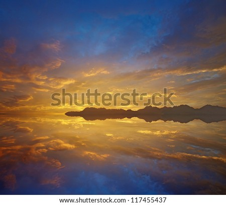 sunset over lake,Dramatic sky with vivid orange and blue cloudscape reflected on the water