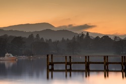 Sunset over Lake Windermere, with woods and mountains in the background.