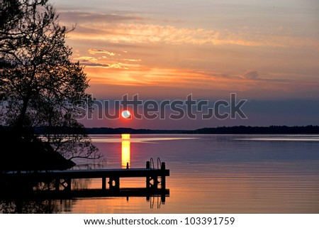 Sunset over lake with silhouette of jetty
