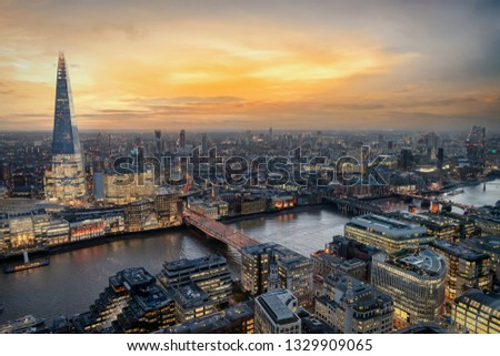 Sunset over London, UK: aerial view to the illuminated skyline along the Thames river with various tourist attractions