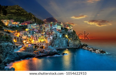 Sunset over Manarola town, one of five famous colorful villages of Cinque Terre National Park in Italy.
