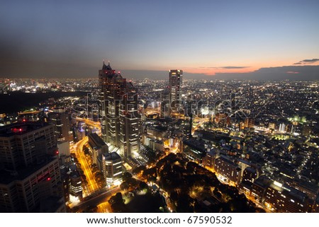 Sunset over modern skyscrapers and illuminated houses over Tokyo, Japan