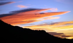 Sunset over mountains. Time-lapse of sun setting over the mountains. Sequence of clouds forming and dissipating near sunset passing by over the sky in Time Lapse at colorful sun set in Spain.