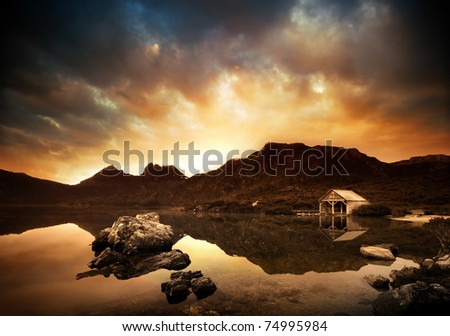 Sunset over peaceful lake with boathouse in the background - stock photo