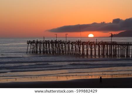 Sunset over Pismo Beach Pier surfers and fishermen on the California coast Zdjęcia stock ©