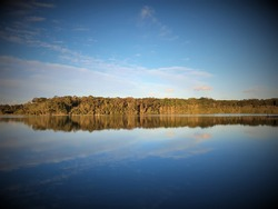 Sunset over Queen Lake, Laurieton, NSW, eucalyptus trees and clouds reflecting off glassy water surface