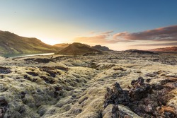 Sunset over Reykjanes peninsula, close to Reykjavik in Iceland, moss grown lava covering the landscape with mountains and a small lake in the background