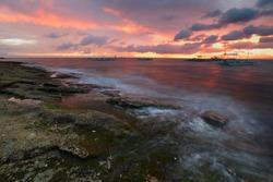 Sunset over rocky coast of Apo island, Philippines