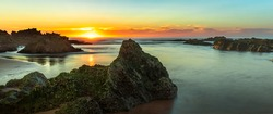 Sunset over rocky coastline with rock formations on the beach
