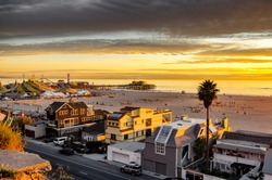 Sunset over Santa Monica beach, expensive beach homes and famous Santa Monica pier, in southern California.