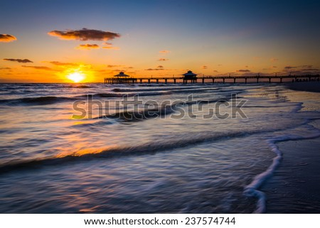 Sunset over the fishing pier and Gulf of Mexico in Fort Myers Beach, Florida.