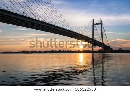 Sunset over the Hooghly river bridge - silhouette view. Vidyasagar bridge is the longest cable-stayed bridge in India. #505122550