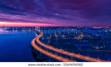 Sunset over the industrial part of the city. Highway. Highway with road bends. Evening view of the motorway. Industrial area. St. Petersburg. Russia. #1064696060