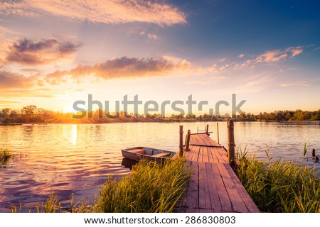Sunset over the lake in the village. View from a wooden bridge, image in the orange-purple toning #286830803