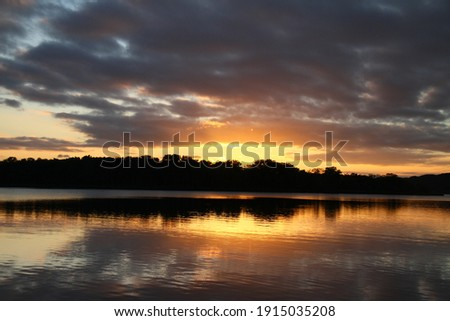 Sunset over the lake, reflecting like a mirror ストックフォト ©