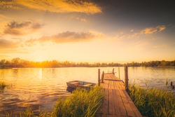 Sunset over the lake with a wooden bridge and boat. View from the shore, image in the yellow toning