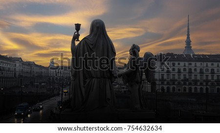 Sunset over the magical Turin. Silhouette of a statue of Faith with a Holy grail in hands and an angel near on a dramatic sky background #754632634