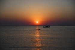 Sunset over the Mediterranean Sea. People on a pleasure boat. The evening sun hangs over the ship. Diver's fins above the water. Girls on deck.