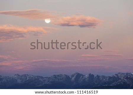 Sunset over the mountain peaks with full moon