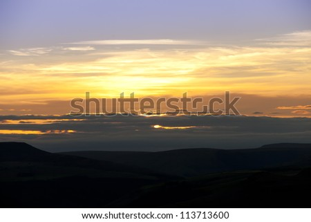 sunset over the mountain range of the peak district national park