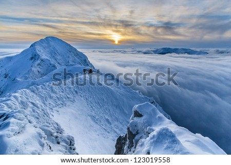 sunset over the mountains and clouds in winter. Piatra Craiului Mountains, Romania